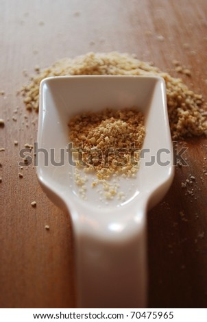 Gomasio in white ceramic container on natural wooden table background