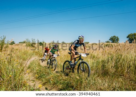 Gomel, Belarus - August 9, 2015: Group of mountain bike cyclists riding in row on track at sunny day, healthy lifestyle active athlete doing sport. - stock photo