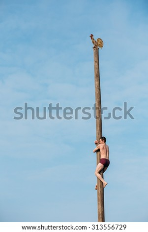 GOMEL, BELARUS - February 21, 2014: Slavic celebration Shrovetide. Young man climbs on a wooden post on traditional holiday dedicated to approach of spring. Blue sky background