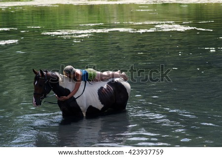 GOMEL, BELARUS - JUNE 24, 2013: Woman bathe horse on a hot summer day.