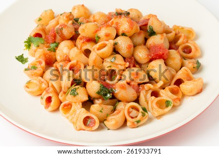 Gomiti elbow pasta shells tossed in arrabbiata tomato, garlic and chili sauce and served with chopped parsley - stock photo