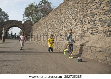 GONDAR, ETHIOPIA - MARCH 25: Unidentified kids play soccer at a street with hand made ball in Gondar, Ethiopia on March 25, 2012. Ethiopian children have to fend for themselves after school. - stock photo