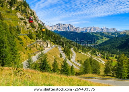 Gondola cars of a lift and view of scenic mountain road in autumn landscape of Dolomites Mountains, Passo Gardena, Italy