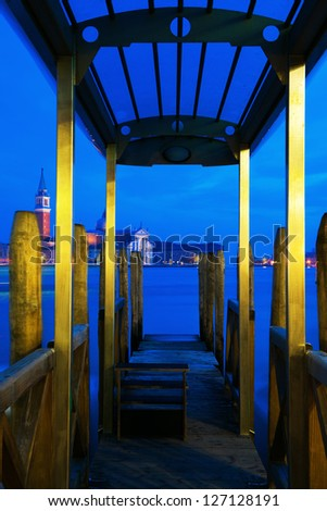 gondola jetty with view on the island of San Giorgio Maggiore at blue night sky