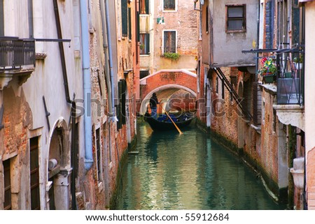Gondola on small canal among old historic houses in Venice, Italy. - stock photo