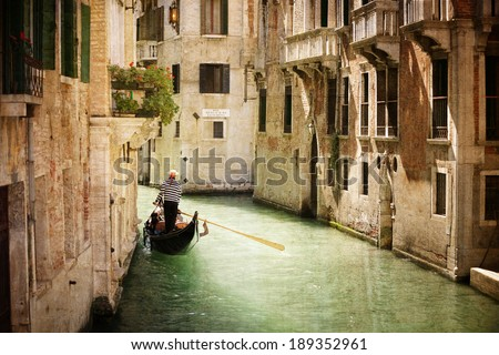 Gondola travels down the canals of Venice in Italy - stock photo