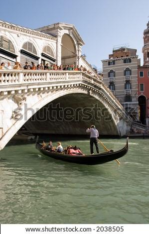 Gondola underneath the rialto bridge in venice - stock photo