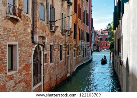 Gondola with gondolier and tourists on a narrow canal in Venice on sunny day, Italy