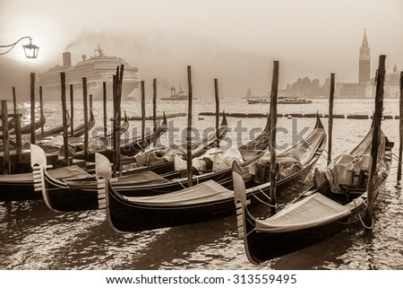 Gondolas at sunrise and a huge cruise ship on the background, Venice, Venezia, Italy, Europe, / sepia tone, monochrome / - stock photo