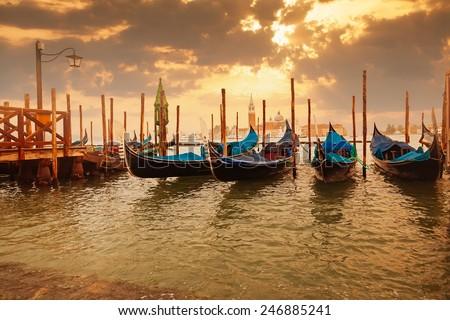 Gondolas at sunset pier near San Marco square in Venice, Italy  - stock photo