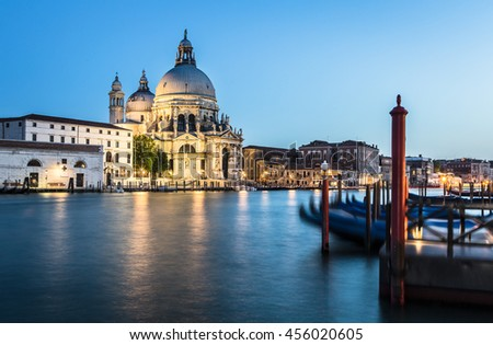 Gondolas captured with motion blur along the Grand Canal at dusk with the Santa Maria della Salute cathedral in the background in the city of Venice in Italy - stock photo