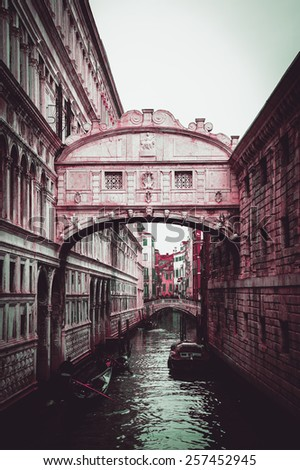 Gondolas floating on canal towards Bridge of Sighs (Ponte dei Sospiri). Venice, Italy. Perspective. Toned dark photo. - stock photo