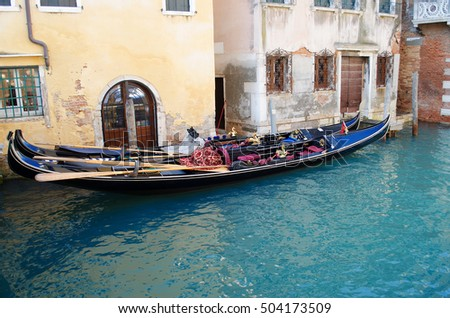 Gondolas in Venice in the narrow channel, Italy. Moored gondolas to the pier near the houses.