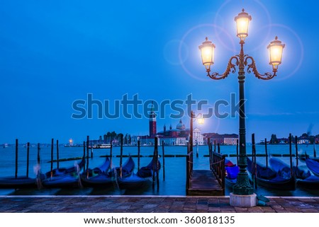 Gondolas in Venice - twilight with San Giorgio Maggiore church. San Marco, Venice, Italy. (filtered, intentional motion blur). - stock photo