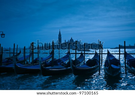 Gondolas moored by Saint Mark's square with San Giorgio di Maggiore church in the background - Venice, Venezia, Italy, Europe - stock photo