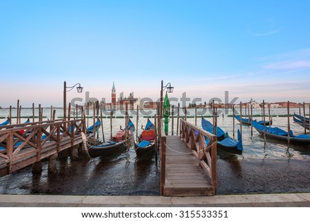 Gondolas moored by Saint Mark square with San Giorgio di Maggiore church in the background - Venice, Venezia, Italy. - stock photo