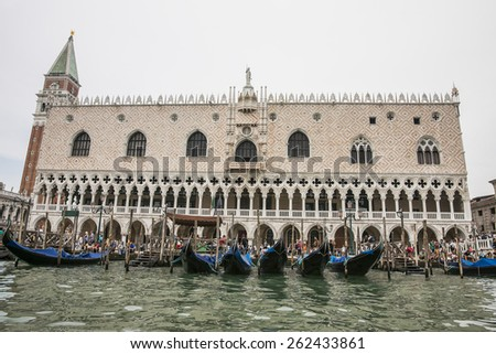 Gondolas parking pier near Doges palace, campanile of St. Marco,  in summer Venice - stock photo