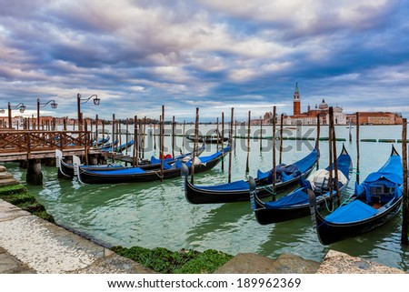 Gondolas tied in a row on Grand canal under evening cloudy sky as San Giorgio Maggiore church on background in Venice, Italy.