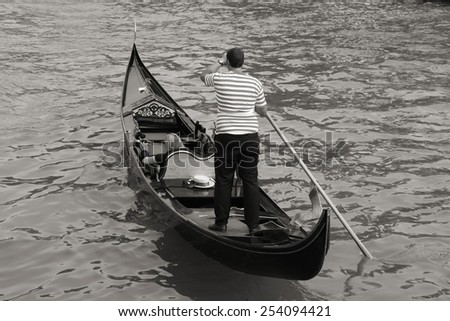 Gondolier and gondola - passenger transportation boats typical for Venice, Italy. Black and white tone. - stock photo