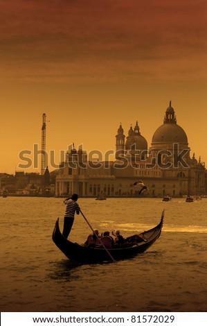 Gondolier at the dusk in Venice, Italy - stock photo