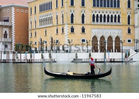 Gondolier navigates the venetian canal - stock photo