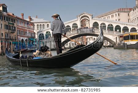 Gondolier, Rialto Bridge, Grand Canal, Venice, Italy - stock photo