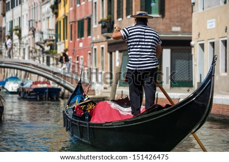 Gondolier traveling down the waterways in Venice - stock photo