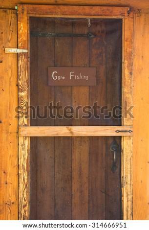 Gone Fishing sign on wooden cabin door  - stock photo