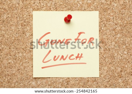 Gone For Lunch handwritten on a sticky note pinned on a bulletin board. - stock photo