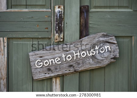 Gone to houston sign on old green door. - stock photo