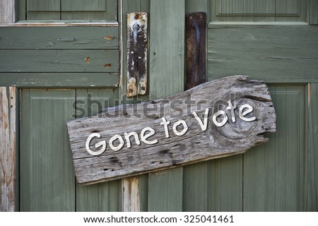 Gone to vote sign on old green doors. - stock photo