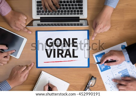 GONE VIRAL Business team hands at work with financial reports and a laptop, top view - stock photo