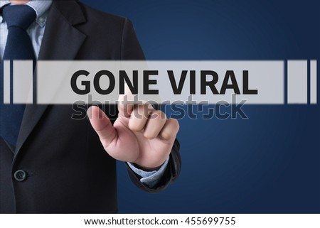 GONE VIRAL Businessman hands touching on virtual screen and blurred city background - stock photo