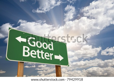 Good, Better Green Road Sign Against Clouds and Sunburst. - stock photo