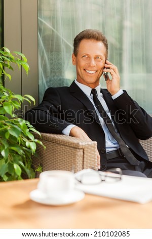 Good business talk. Cheerful mature man in formalwear talking on the mobile phone and smiling while sitting at the chair outdoors with coffee cup on foreground - stock photo