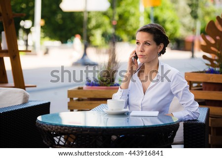 Good business talk. Cheerful young businesswoman talking on the mobile phone and holding cup of coffee while sitting outdoors - stock photo
