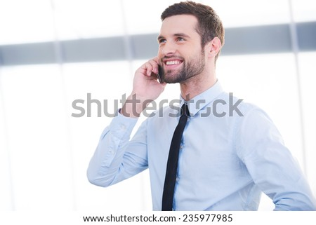 Good business talk. Confident young businessman talking on the mobile phone and smiling while standing indoors - stock photo