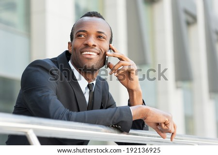 Good business talk. Happy young African man in formal wear talking on the mobile phone and smiling while standing outdoors - stock photo