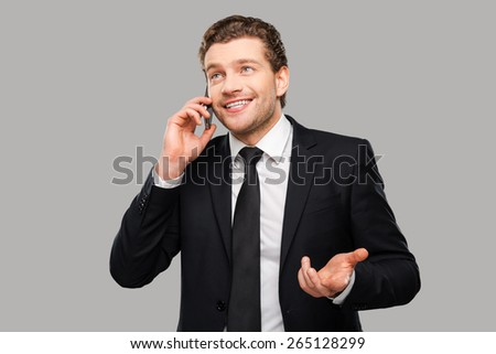 Good business talk. Portrait of confident young man in formalwear talking on the mobile phone and smiling while standing against grey background - stock photo
