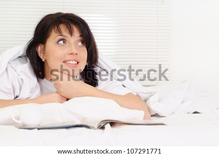 Good Caucasian girl lying in bed on a light background