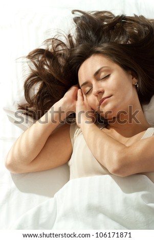 Good Caucasian woman lying on a pillow on a light background - stock photo