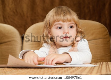 Good Caucasian young baby draws a table on a brown background