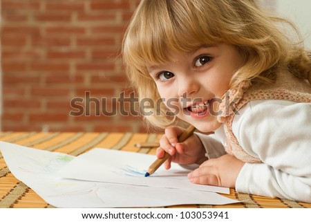 Good Caucasian young girl draws a table on a brown background