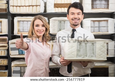 Good choice. The young salesman and the customer with quality mattresses in the store. - stock photo