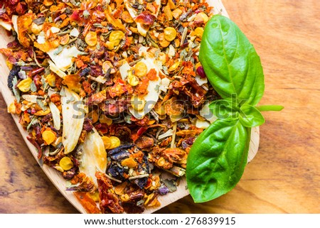 Good cuisine. Closeup colored spices for pasta mix and fresh basil leaf on wooden spoon