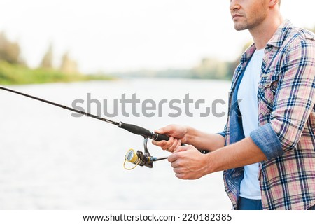 Good day for fishing. Confident young man fishing while standing on quayside  - stock photo