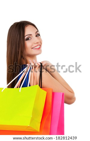 Good day for shopping. Beautiful young woman in blue dress holding shopping bags and smiling at camera - stock photo