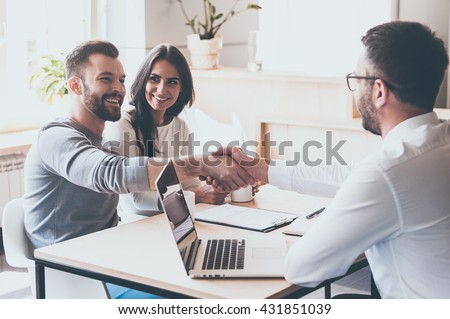 Good deal! Cheerful young man bonding to his wife while shaking hand to man sitting in front of him at the desk  - stock photo