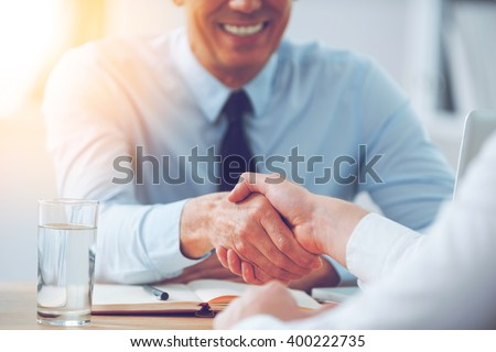 Good deal. Close-up of two business people shaking hands while sitting at the working place - stock photo
