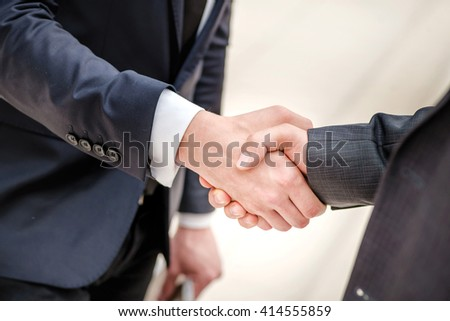 Good deal! Two young businessman standing opposite each other and shake their hands. Young people smiling into the camera. Close-up view below - stock photo